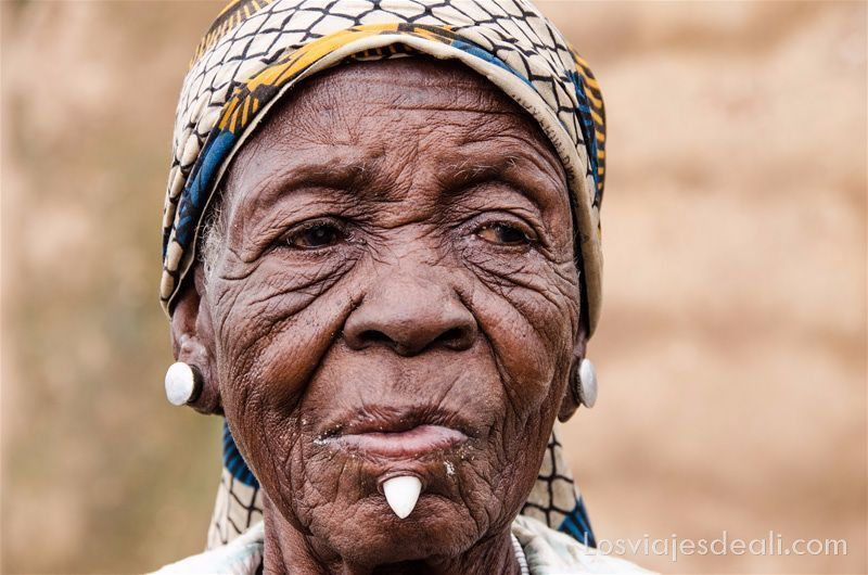 mujer anciana con muchas arrugas y piercings de cuarzo en las orejas y en la barbilla debajo del labio