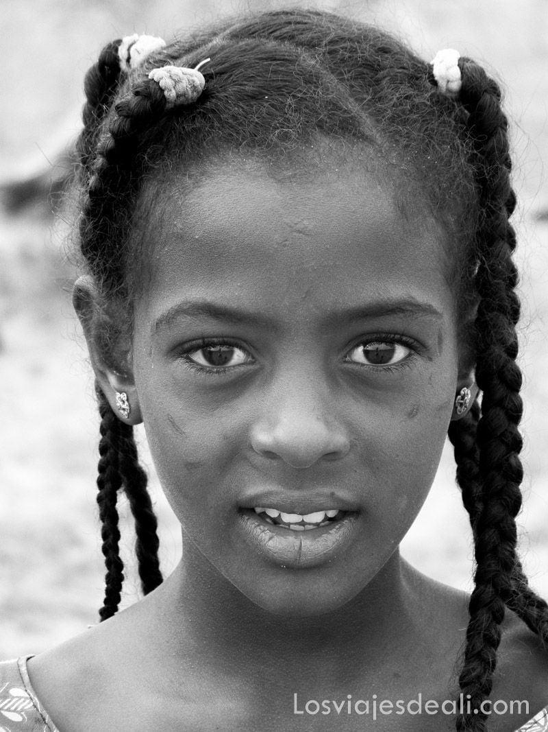 niña de Burkina Faso en blanco y negro con señales en la cara que son escarificaciones para mostrar de qué familia es