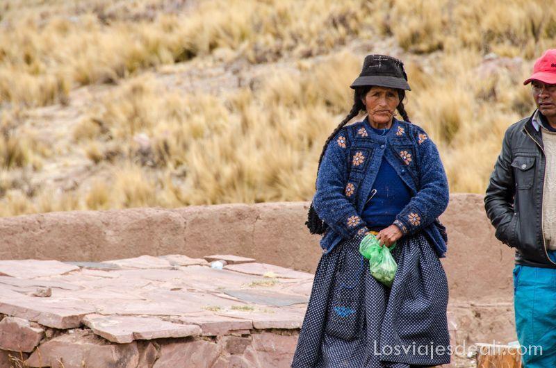 mujer peruana con largas trenzas, y falda, cogiendo hojas de coca de una bolsa de plástico verde.