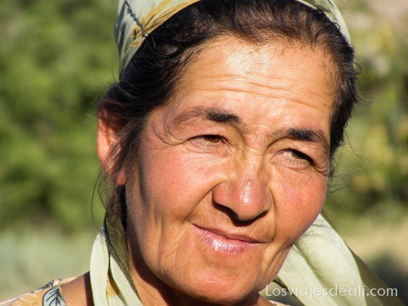 mujer uzbeka de mediana edad con pañuelo en la cabeza cogido con horquillas, mirada hacia un lado y ligera sonrisa, iluminada con sol de atardecer