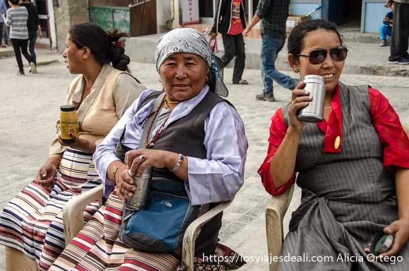 mujeres tibetanas con delantales de rayas de colores tomando su té en la calle en Leh