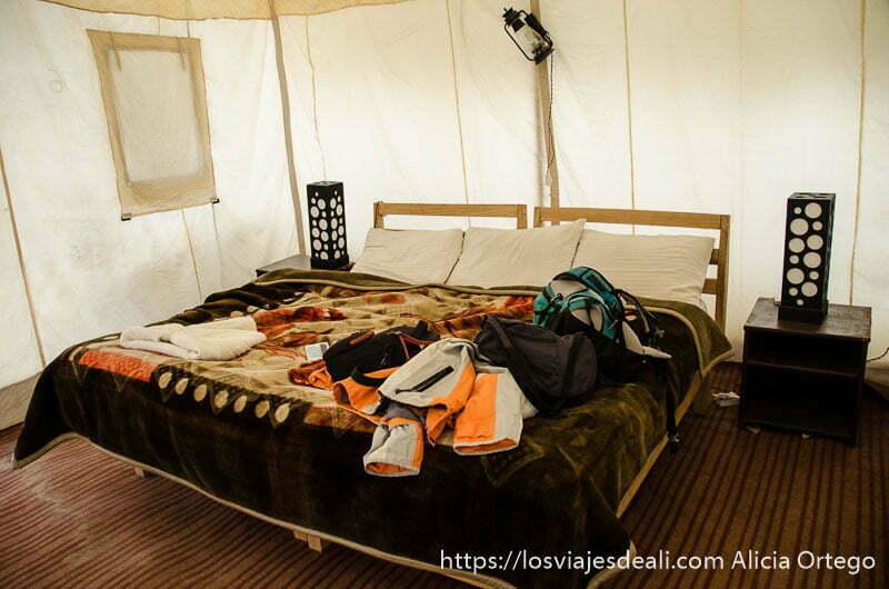 cama con mesillas en el interior de tienda de campaña del lago pangong