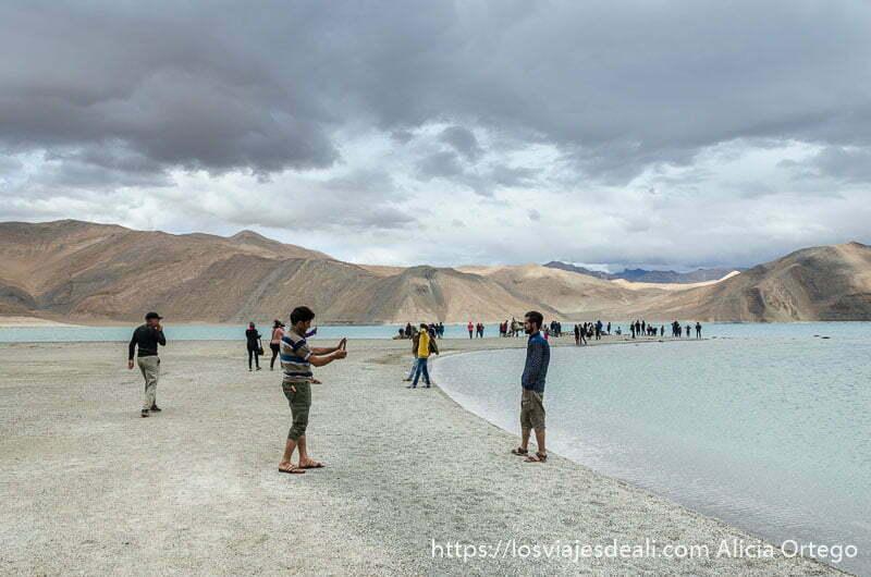 turistas indios posando en la orilla del lago pangong