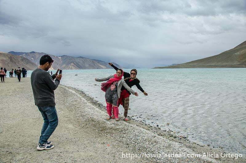 dos mujeres indias postureando en la orilla del lago pangong mientras su amigo hace foto con el móvil
