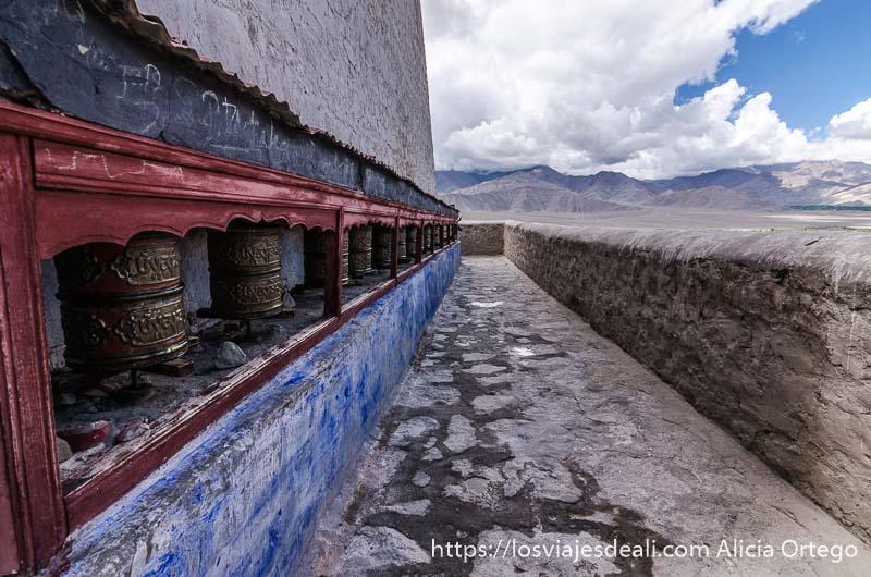 pared con línea de molinos de oraciones frente a balcón al valle del indo
