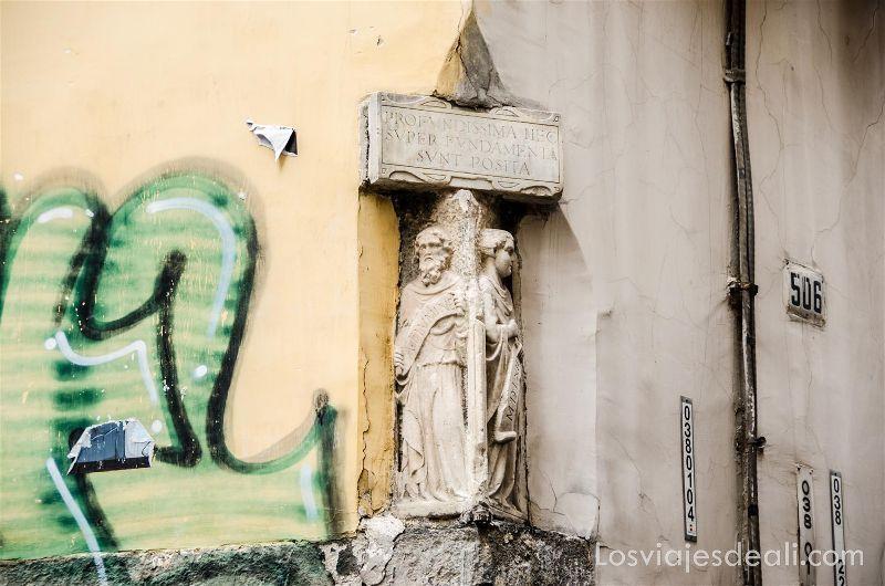 esquina donde hay dos figuras de piedra que parecen santos y un cartel escrito en latín