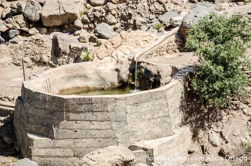 canal de agua que llega a un depósito de ladrillo en la cordillera al hajar