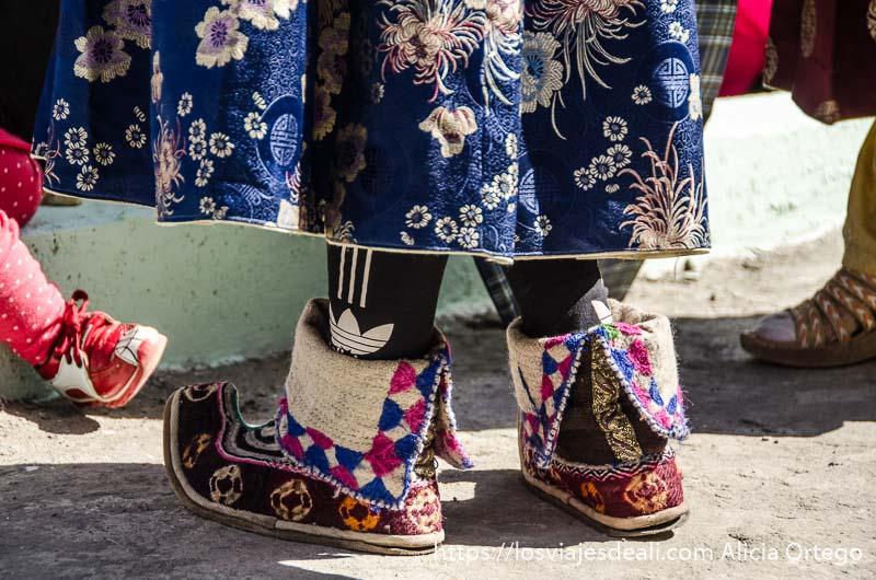pies calzados con zapato tibetano bordado de colores y calcetines de adidas