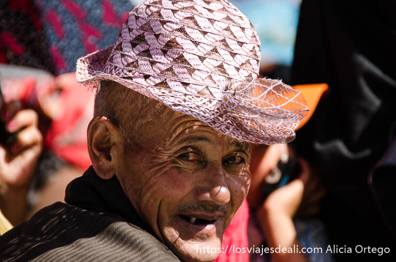 anciano tibetano con un gorro de señora de color rosa en una conferencia del dalai lama
