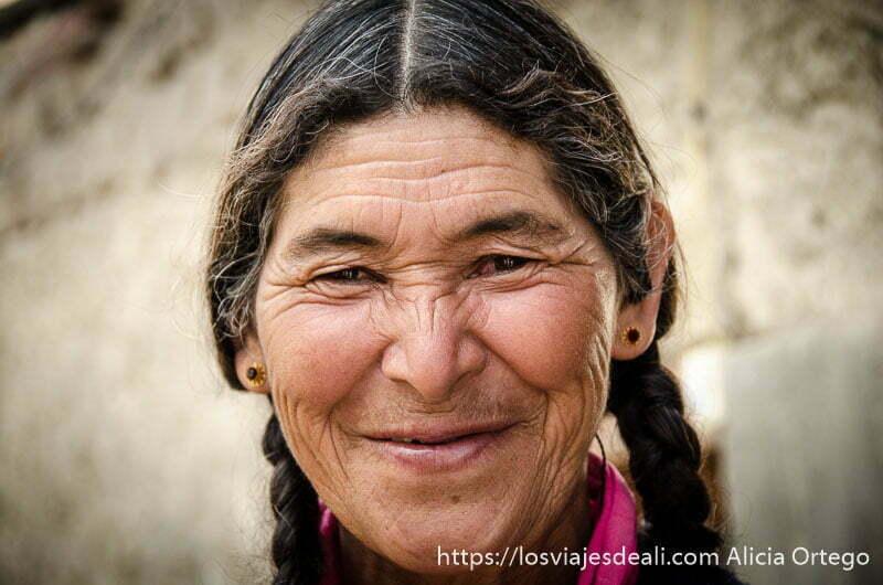 retrato de anciana sonriente con trenzas trekking cerca de leh