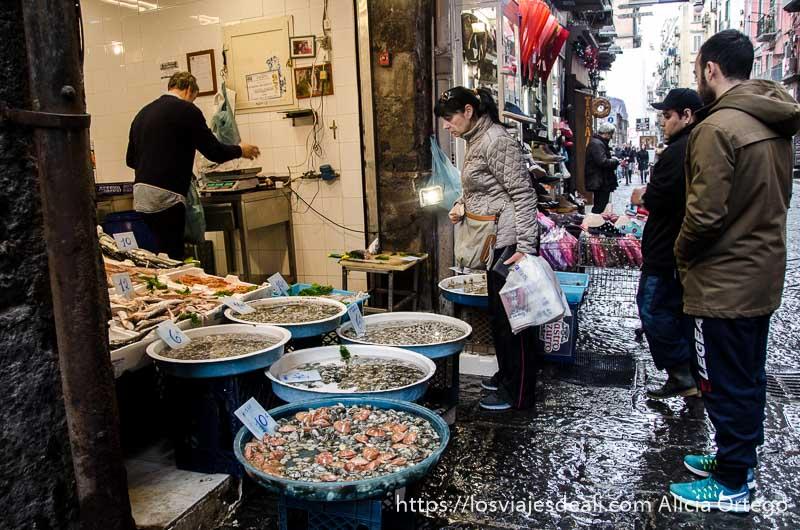 pescadería abierta a la calle con clientes comprando paseos por nápoles