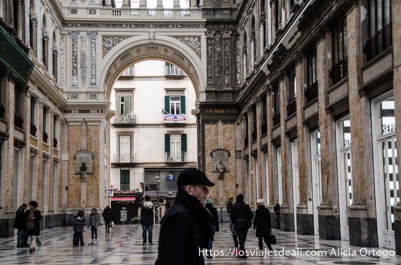 hombre con gorra pasando cruzando galería umberto paseos por nápoles
