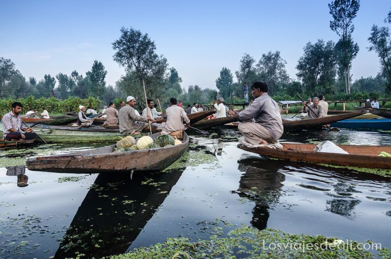 barcas con calabazas y hombres comerciando en el mercado flotante de Srinagar