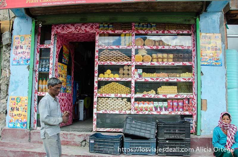 escaparate de pastelería abarrotado de dulces y hombre pasando delante en drass uno de los pueblos de cachemira