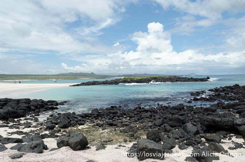 playa de aguas turquesas y rocas volcánicas con arena blanca en isla san cristóbal galápagos