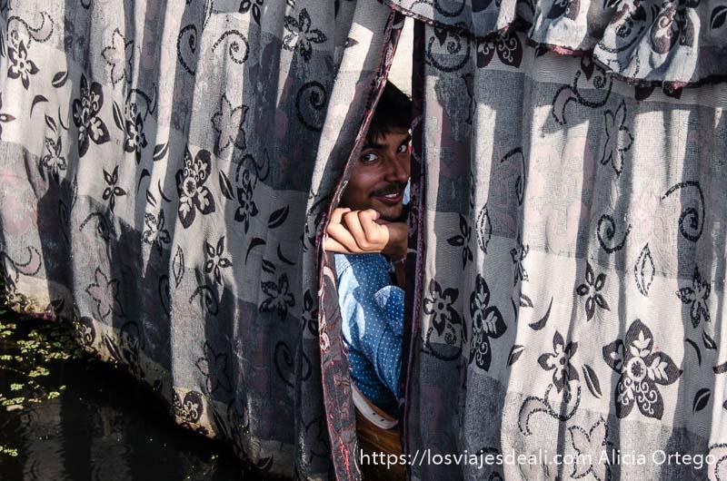 chico asomándose por la cortina de una barca, sonriente en srinagar