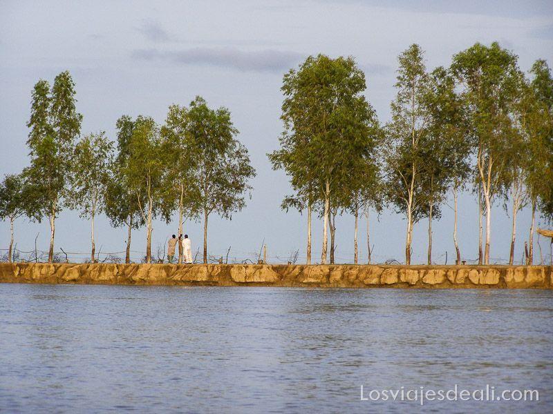 un pueblo del río niger con agua color gris porque refleja las nubes