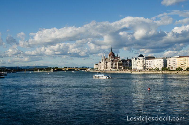 parlamento de budapest con río danubio muy ancho y barco navegando