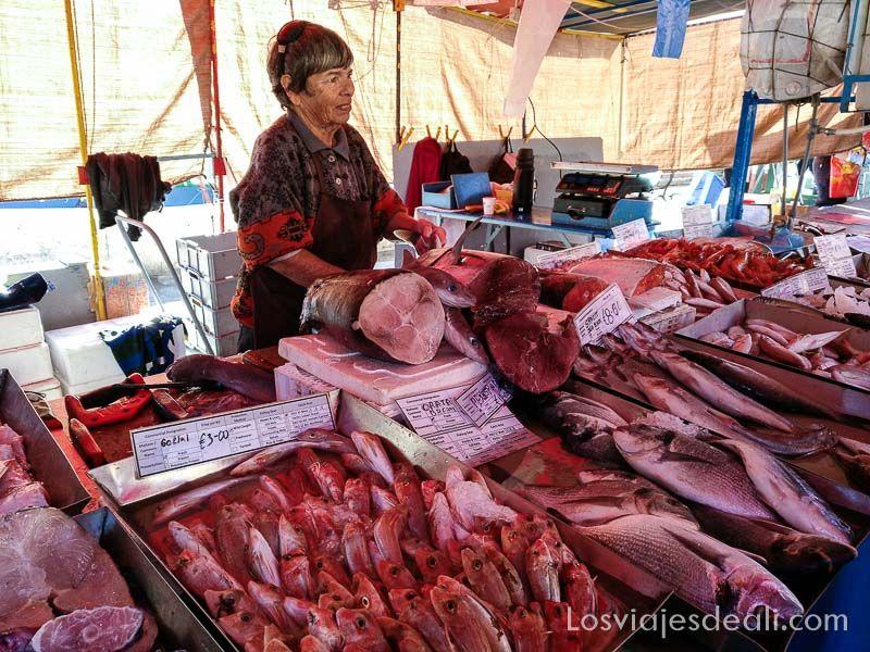 pescadera en su puesto del mercado con grandes piezas de atún y otros pescados alrededor