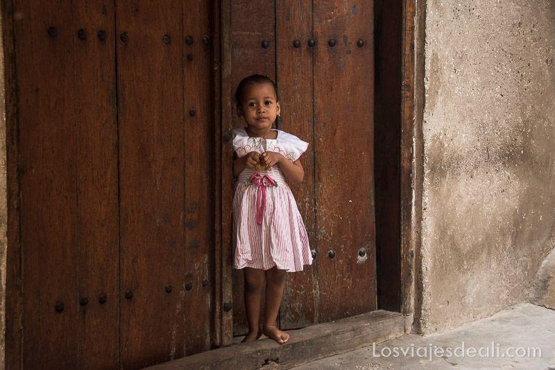niña asomando por puerta en Stone Town Zanzíbar los viajes y el tiempo