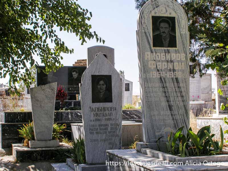 tumbas de mármol blanco con letras en ruso y foto grande de cada difunto serigrafiada en la piedra