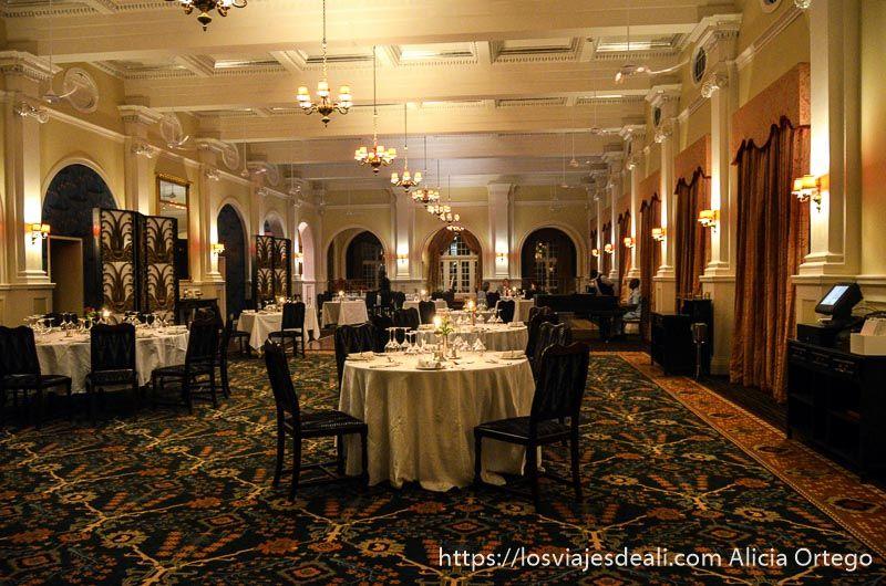restaurante del hotel cataratas victoria con gran alfombra, lámparas colgantes y mesas redondas con manteles blancos