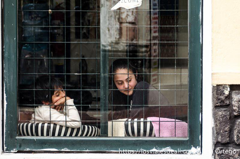 niños mirando la calle desde el otro lado del cristal en quito puertas y ventanas del mundo