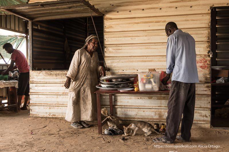 tabernero de sudán habla con un cliente apoyado en la pared de chapa de su chiringuito