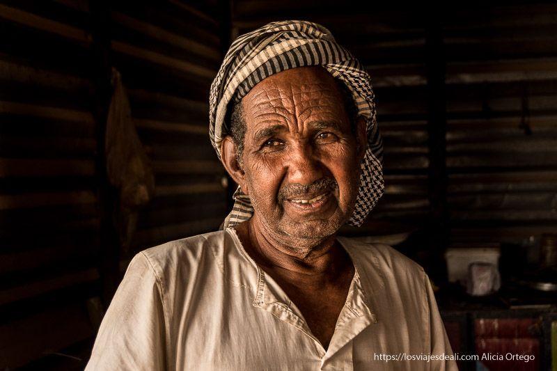 tabernero de Sudán con pañuelo de cuadros en la cabeza sonríe mirando al infinito gentes de Sudán