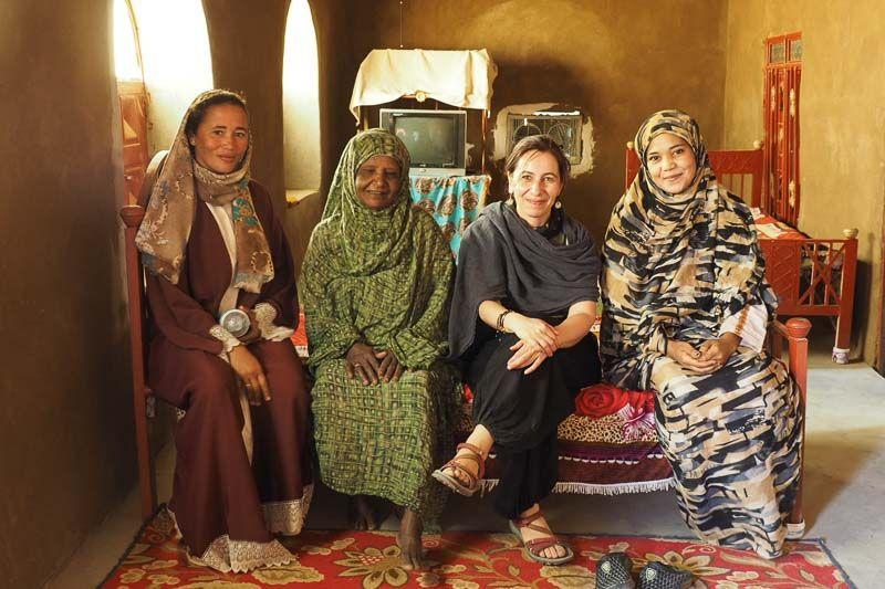 tres mujeres sudanesas y yo misma sonriendo a la cámara en una casa nubia guía de viaje a Sudán