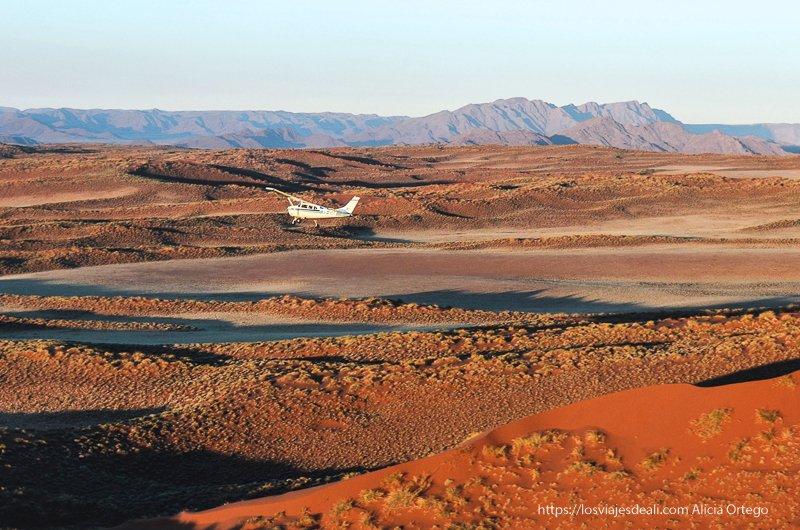 vuelo en avioneta en el desierto del Namib al atardecer con montañas al fondo