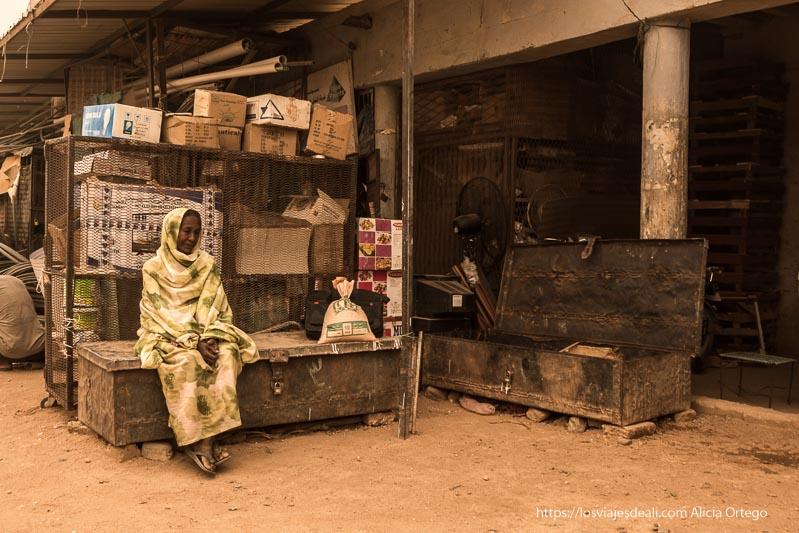 mujer sentada junto a una tienda del mercado de karima en Sudán