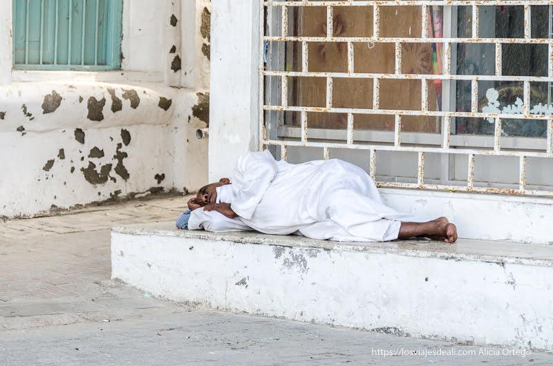 hombre echando la siesta en las calles de Muscat