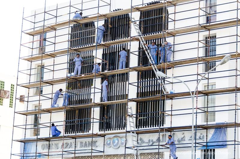 andamios con obreros vestidos de azul en Muscat Omán
