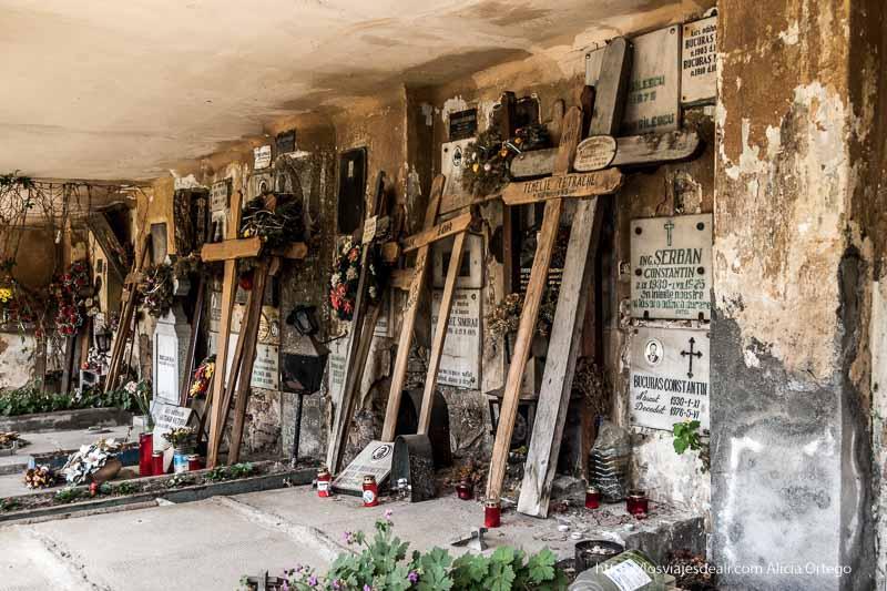 cementerio de la iglesia de san nicolás con grandes cruces apoyadas en la pared de nichos