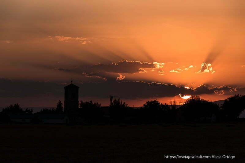 atardecer con campanario a contraluz y sol semitapado por nubes rojas