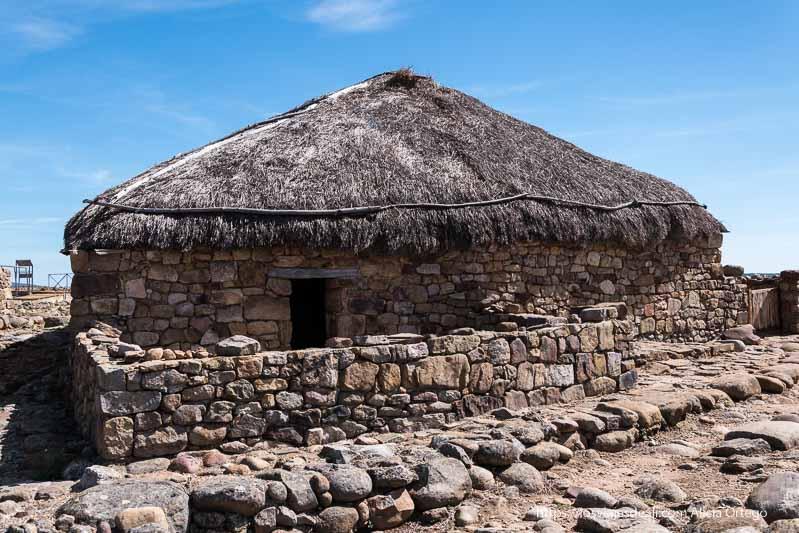 casa celtíbera con muros de piedra y techo de paja en el yacimiento de numancia