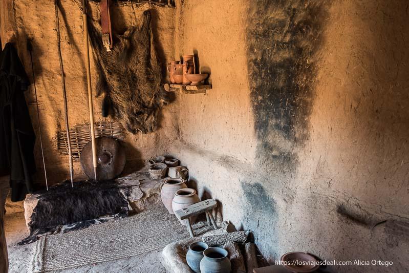interior casa celtíbera con cerámica, armas y pieles soria romana