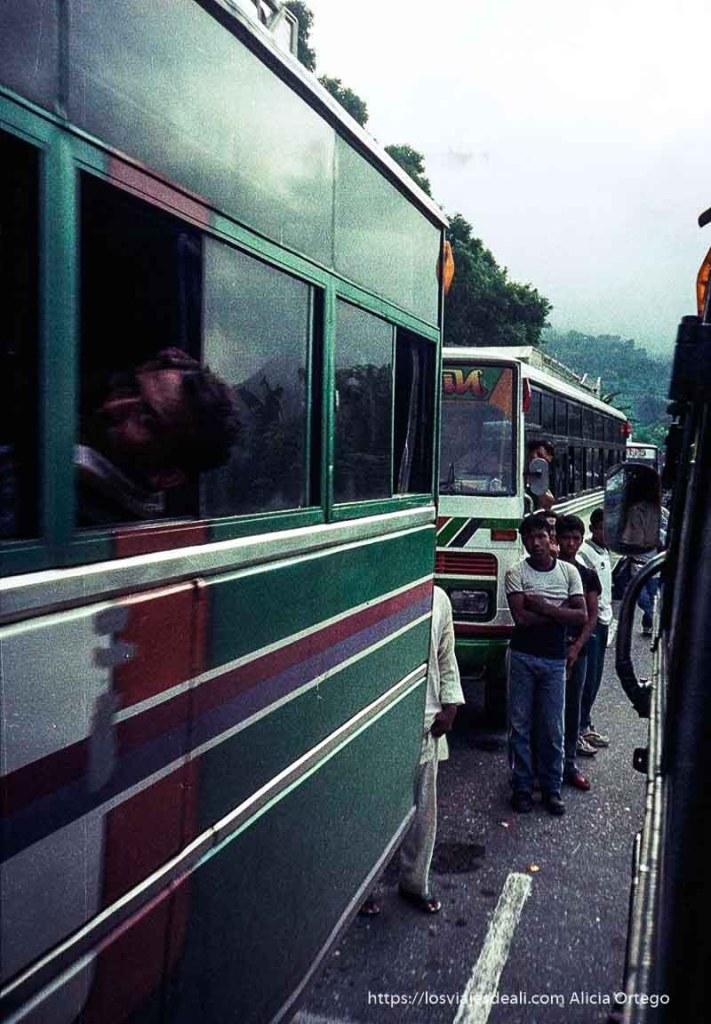 fila de autobuses con hombre sacando la cabeza por la ventanilla y otros mirando la cámara fijamente nepal