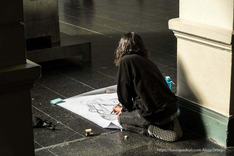 estudiante dibujando en el suelo una estatua del museo de bellas artes de santiago de chile