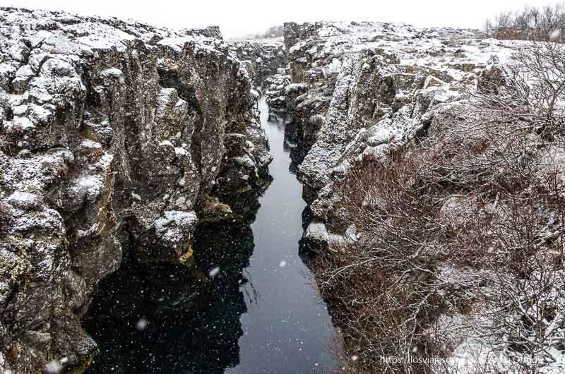 río que discurre entre paredes de roca bajo nevada triángulo dorado de islandia