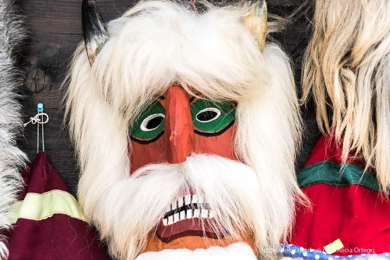 máscara rumana de madera con cara naranja y cuernos que salen del pelo blanco excursión a bran y rasnov