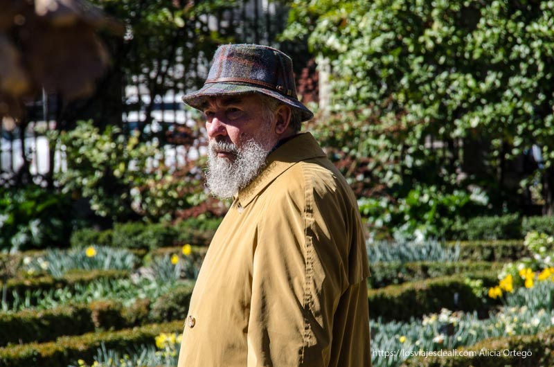 señor con gabardina amarilla, gorro de cuadros y barba blanca en el real Jardín Botánico de Madrid