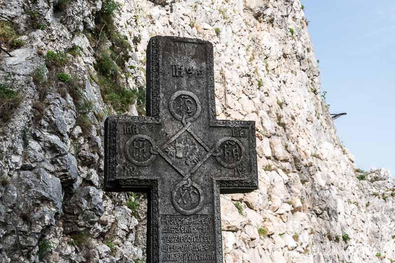 cruz de piedra con símbolos y grafía rumana junto a la puerta del castillo excursión a bran y rasnov
