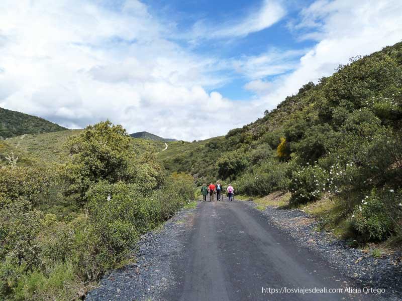 camino de la ruta con tres personas al fondo y cielo azul con nubes