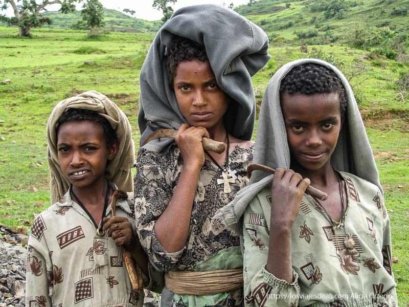 tres niños con sus hoces al hombro de camino a gondar