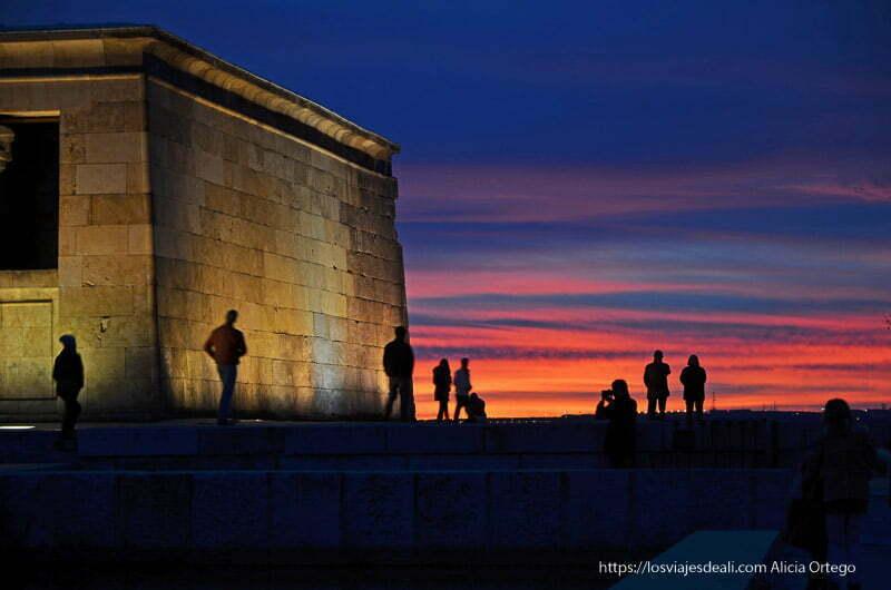 siluetas de gente al lado del templo de debod con cielo azul y rojo, uno de los atardeceres del mundo que más me gustan