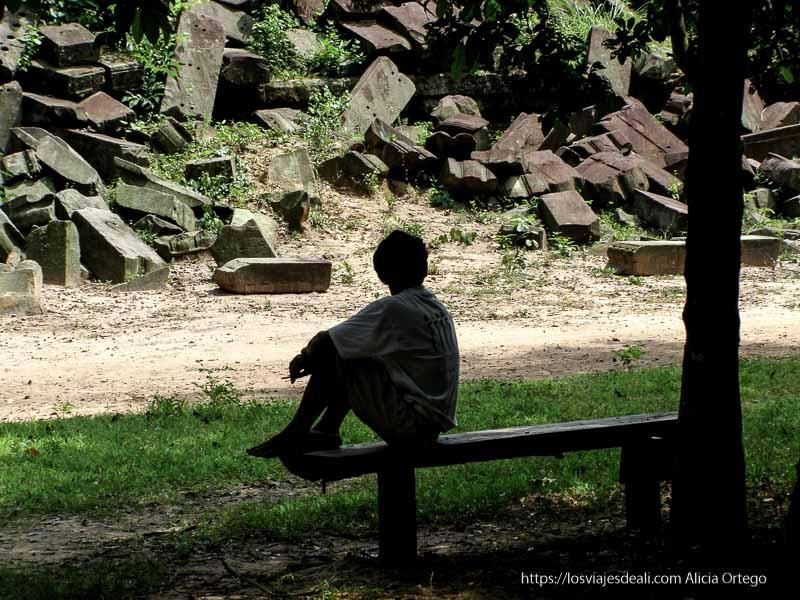 niño sentado en un banco a contraluz mirando las piedras de beng mealea