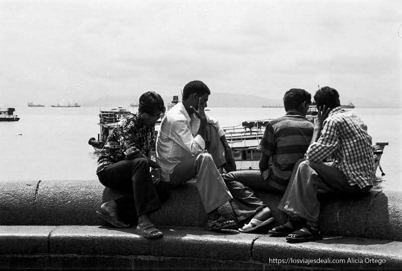 cuatro hombres sentados mirando al mar en bombay
