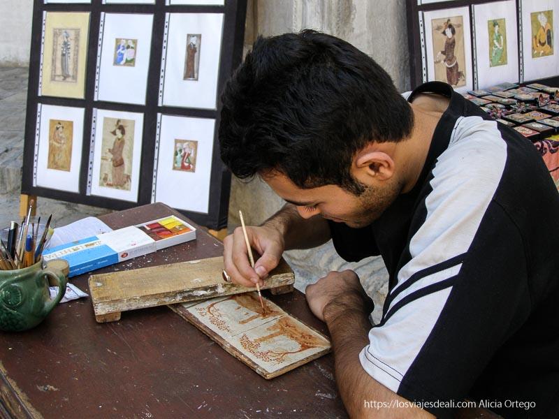 artesano pintando miniatura en bukhara